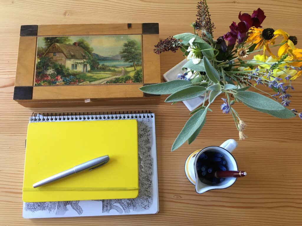 Photo of fountain pens, notebooks and a vase of flowers on a wooden table.
